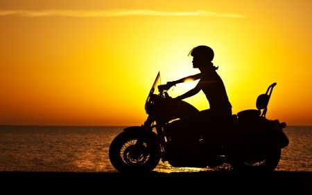 14634529 - woman biker over sunset, female riding motorcycle, motorbike driver traveling, girl racing on the beach road, freedom lifestyle