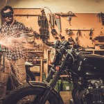 36331976 - mechanic doing lathe works in motorcycle customs garage
