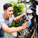 37846984 - asian man washing his motorcycle or scooter with soap and sponge