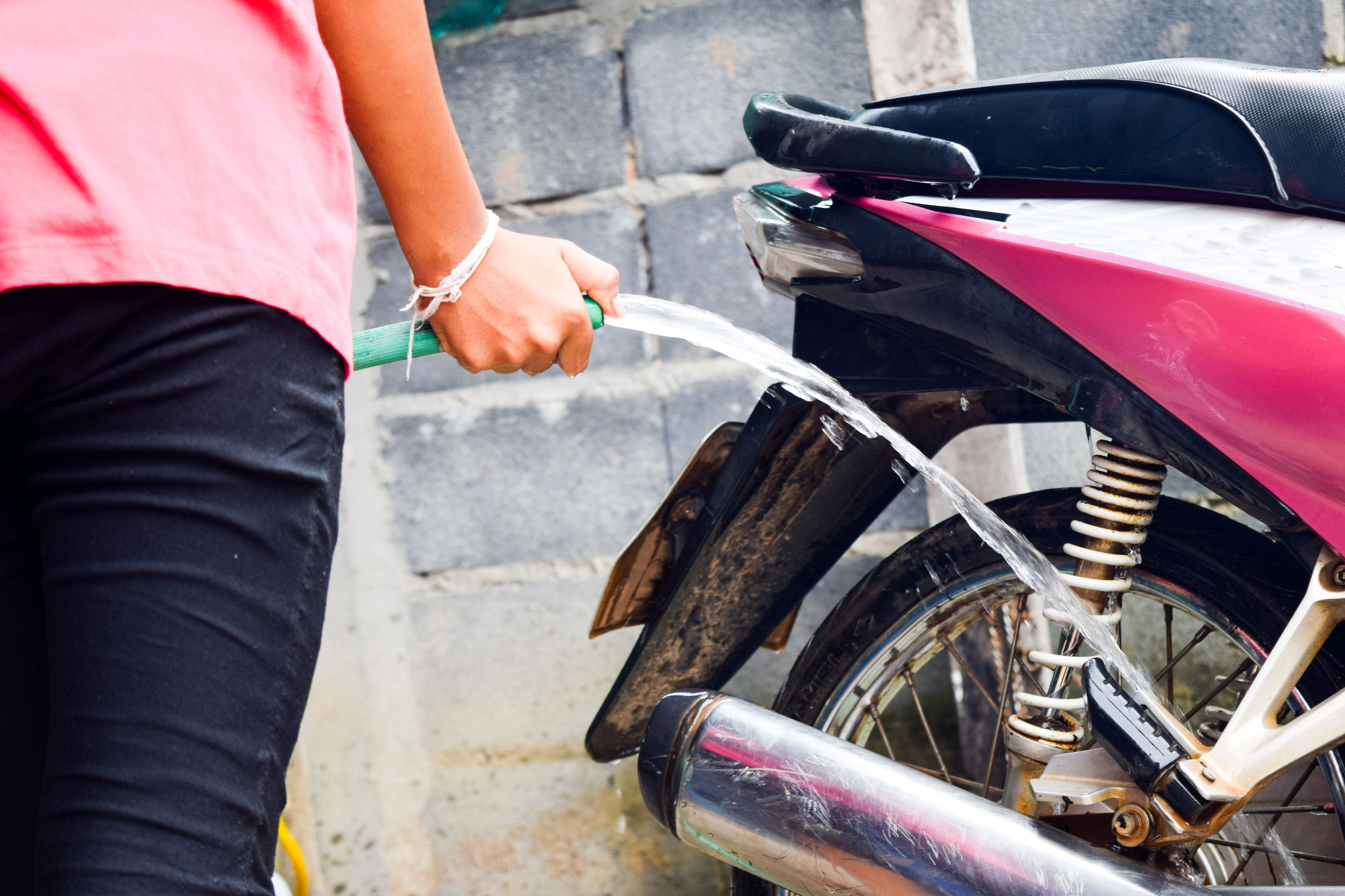 65137743 - girl cleaning and washing the pink motorcycle