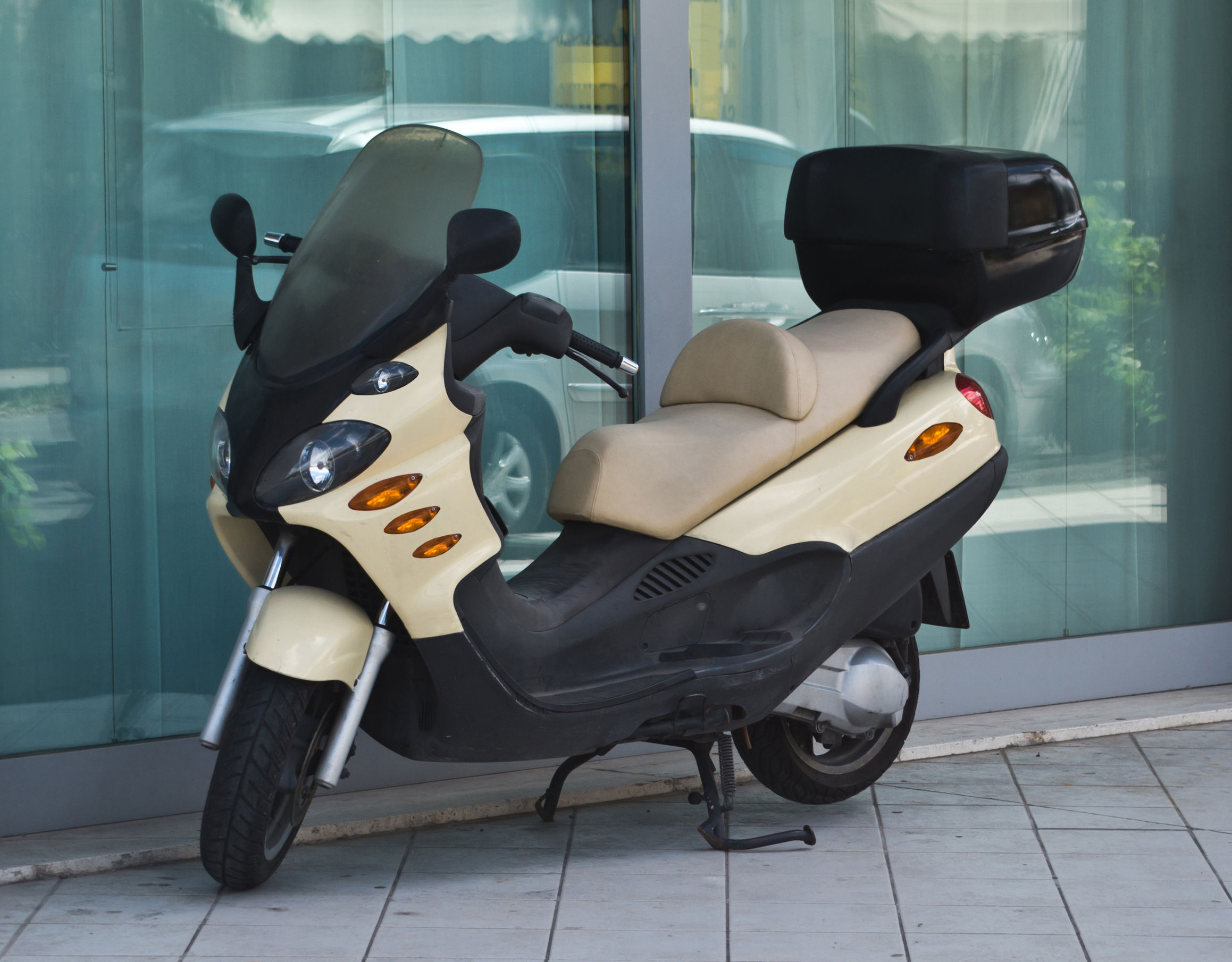68936746 - futuristic scooter with light brown trunk parked on the sidewalk