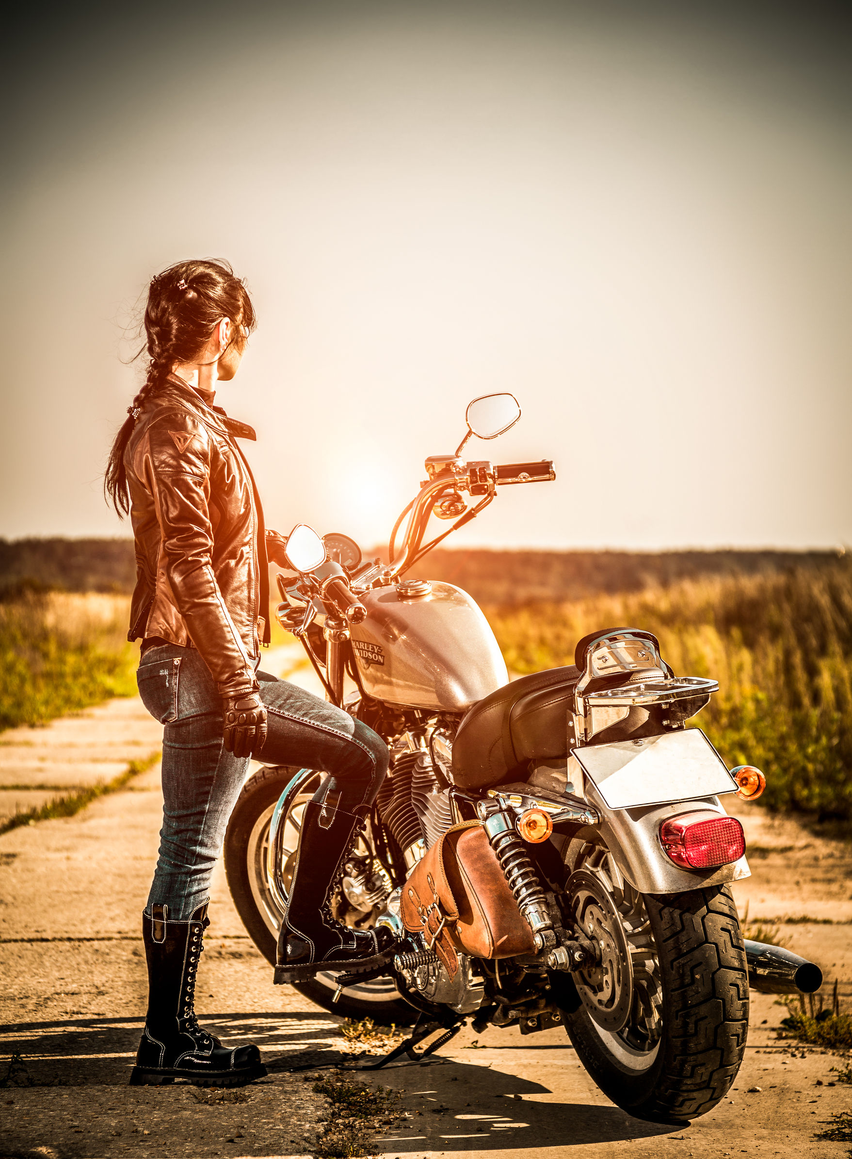 28360792 - russia-july 7, 2013: biker girl and bike harley sportster. harley davidson sustains a large brand community which keeps active through clubs, events, and a museum. filter applied in post-production.