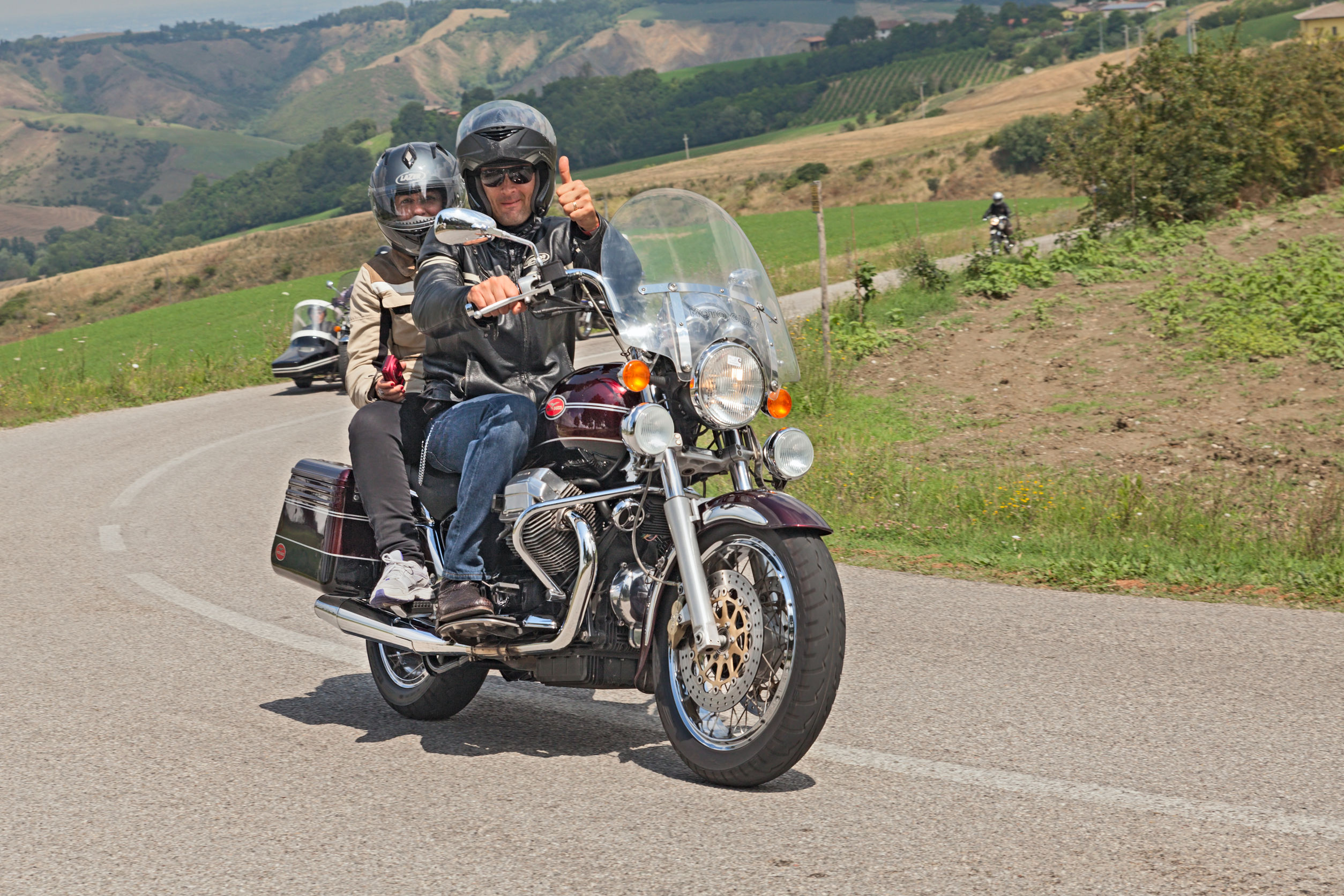 30036861 - couple of bikers riding a vintage italian motorcycle moto guzzi california classic at rally ix moto guzzi memorial zigolo on july 13, 2014 in meldola, fc, italy