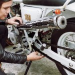88023444 - confident asian man wearing black leather jacket sitting on haunches while adjusting chain of vintage motorcycle