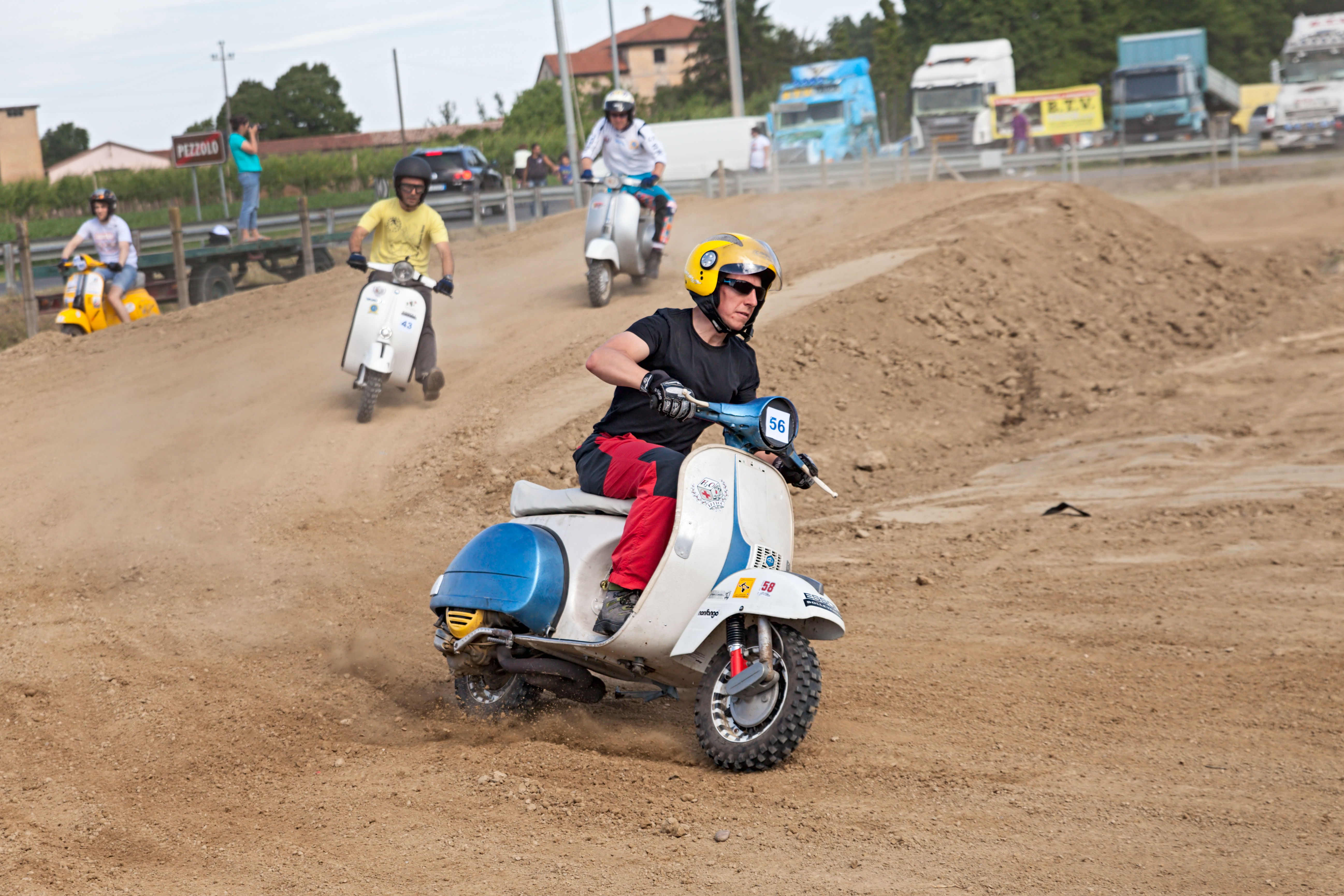"""Vespa cross: a motocross rider engaged in curve on the motocross track riding a vintage italian scooter during the motor festival """"Festa de mutor"""" on June 9, 2013 in Pezzolo di Russi, RA, Italy"""