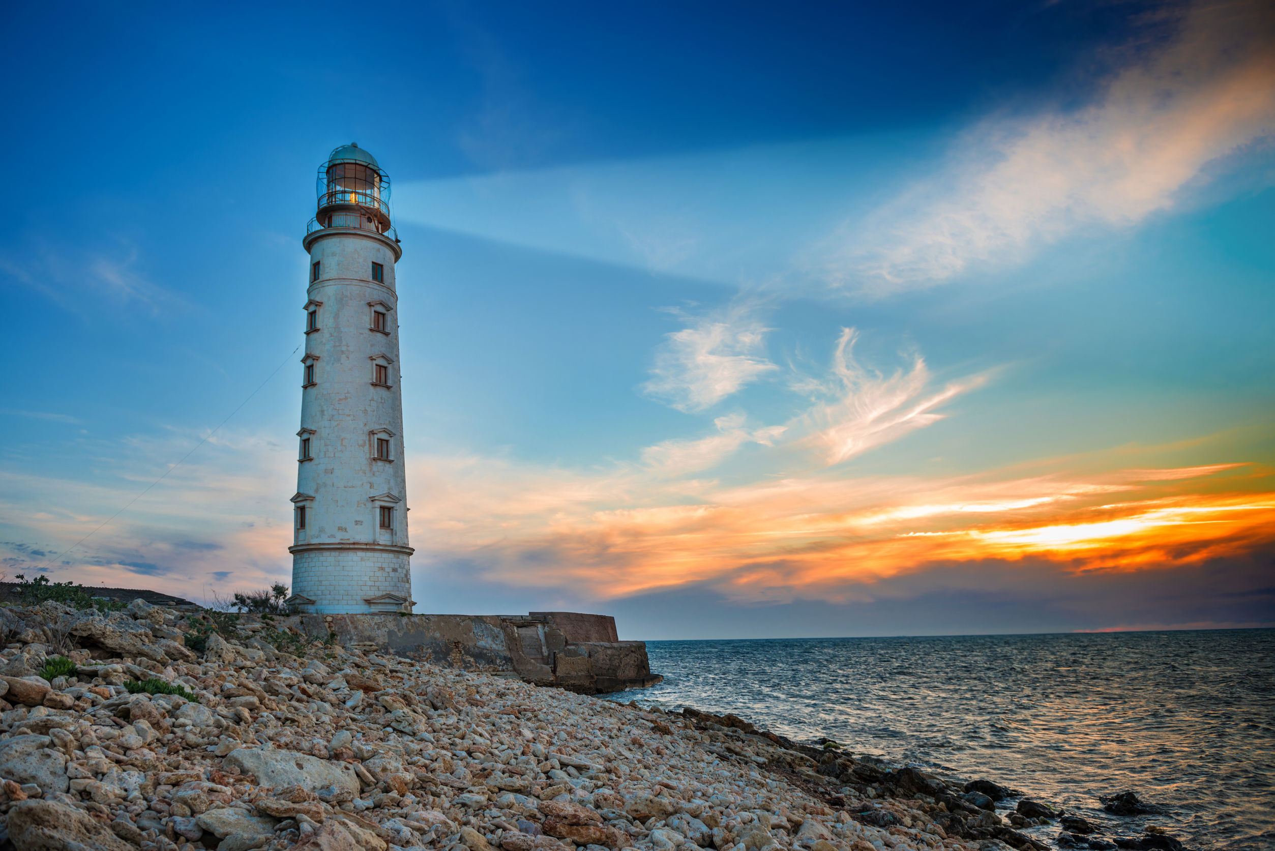 39704848 - lighthouse searchlight beam through sea air at night. seascape at sunset